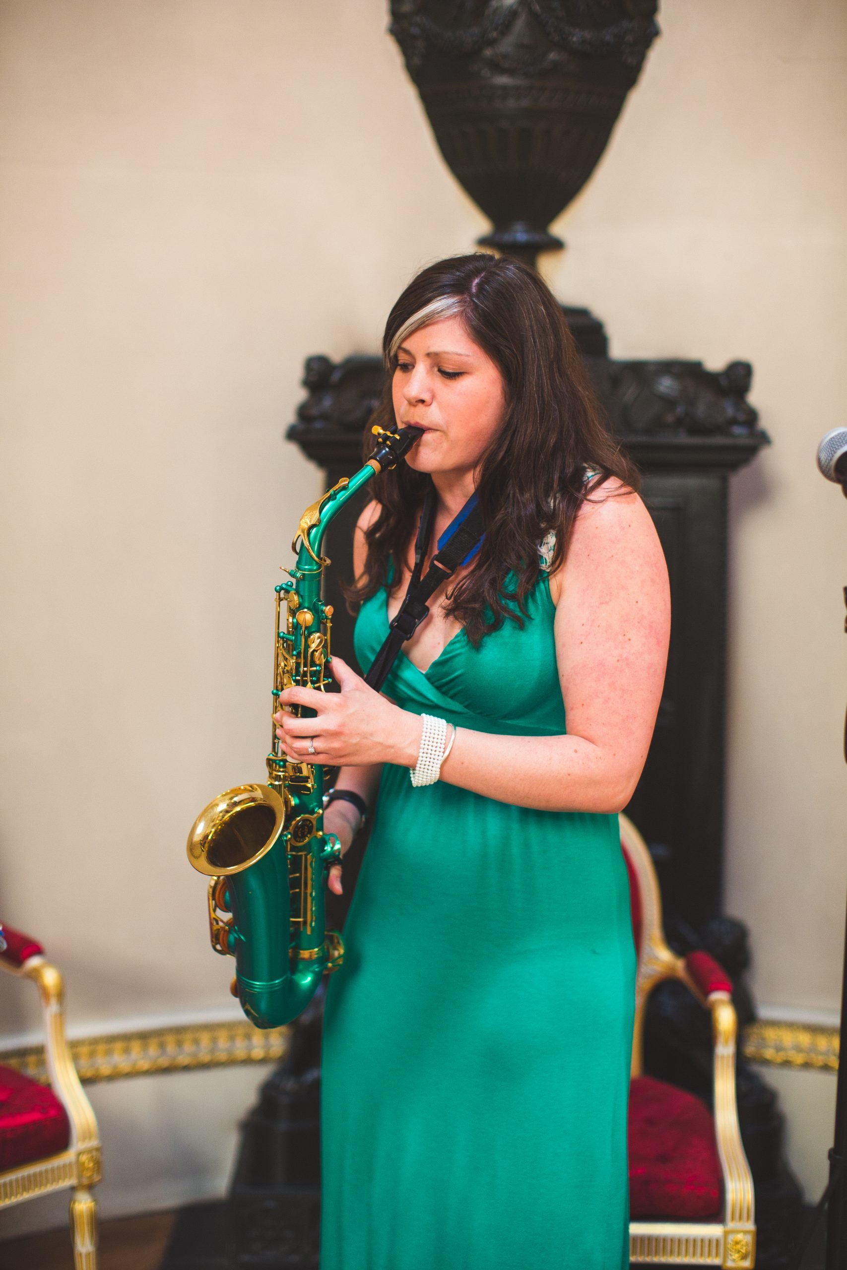 saxophone player wearing green dress playing green saxophone